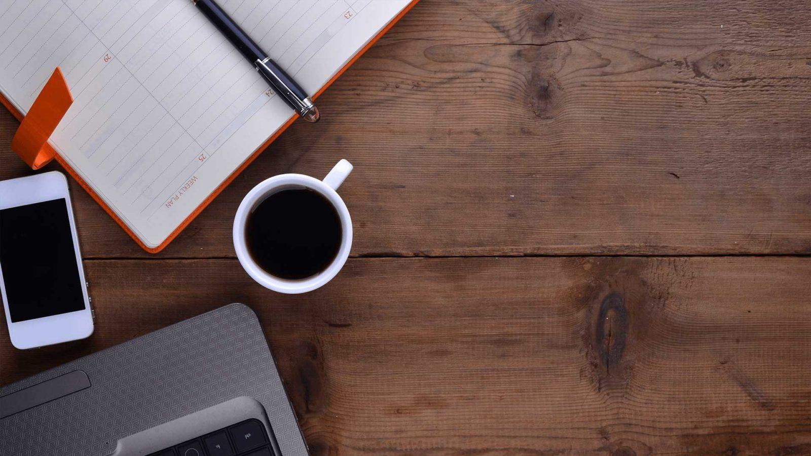 Työpöytä, jossa näkyy mm. kahvikuppi, tietokone, puhelin
